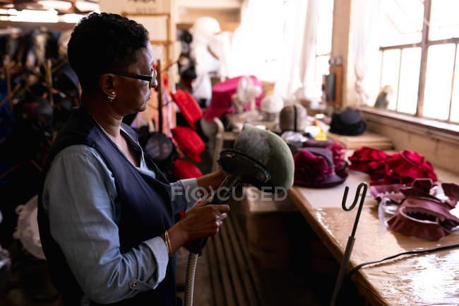 Вид збоку крупним планом середнього віку змішана гонка жінка перевірка і операційна машина для пари чистої капелюх вона тримає, стоячи на столі в майстерні на заводі капелюх, інші капелюхи видно у фоновому режимі — стокове фото