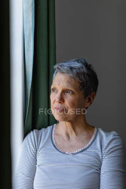 Передний вид крупным планом зрелой кавказской женщины с короткими седыми волосами стоя и глядя в окно дома — стоковое фото