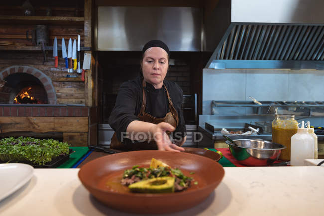 Front view close up of a young Caucasian female chef presenting a finished dish ready to be served, in a busy restaurant kitchen — Stock Photo