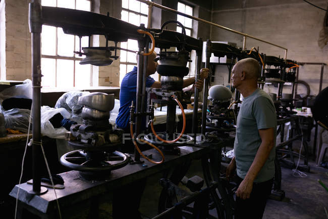 Side view of a senior and a middle aged mixed race men working together at a machine in the workshop at a hat factory — Stock Photo