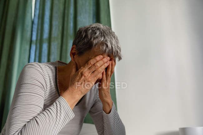 Зовнішній вигляд крупним планом зрілої кавказької жінки з коротким сивим волоссям сидять вдома з закритими шторами, головою її в руках — стокове фото