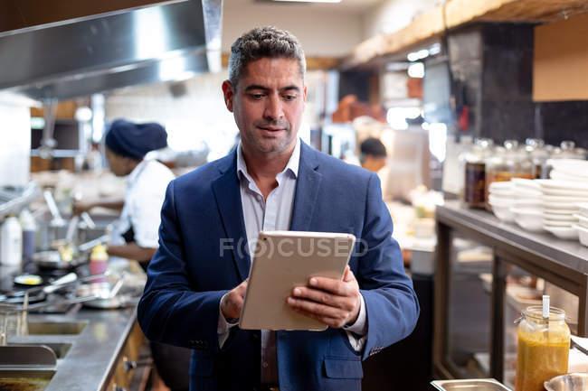 Vista frontale da vicino di un gestore di un ristorante caucasico di mezza età utilizzando un tablet in una cucina ristorante occupato, mentre il personale di cucina lavora sullo sfondo — Foto stock