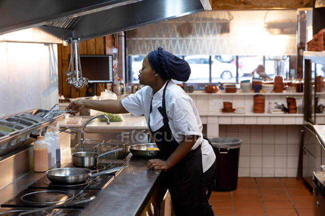 Side view close up of a young African American female chef reaching for ingredients at a cooking station in a restaurant kitchen — Stock Photo