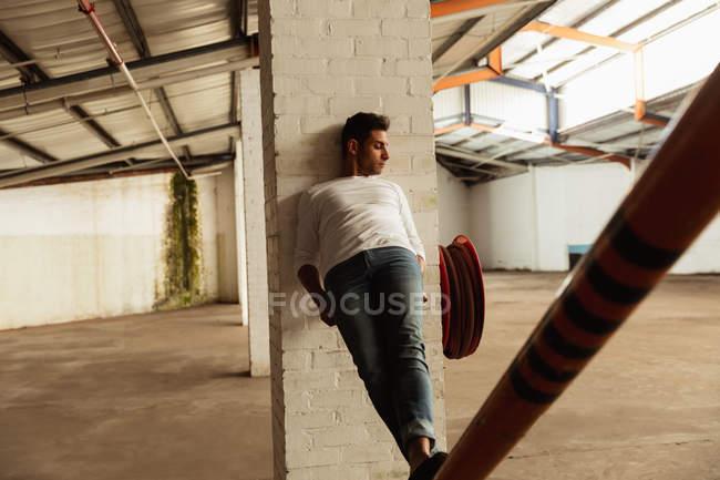 Вид спереди на молодого артиста балета, стоящего на структурном столбе и опирающегося на колонну в пустой комнате на заброшенном складе — стоковое фото