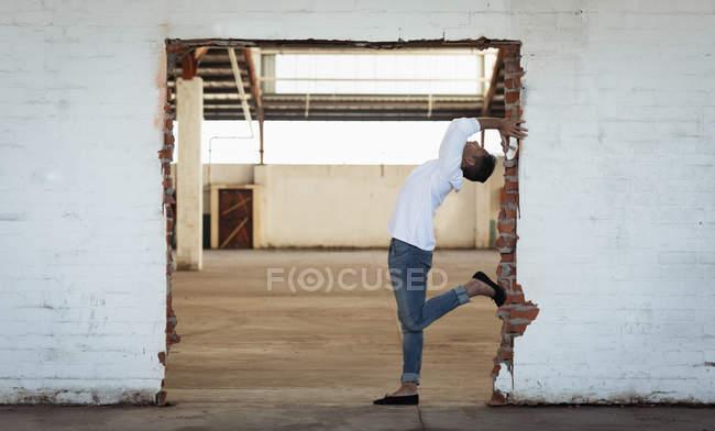 Вид сбоку на молодого артиста балета в джинсах, позирующего в дверях в пустой комнате на заброшенном складе — стоковое фото