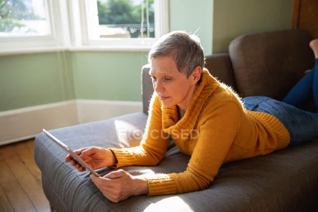 Вид сбоку зрелой кавказской женщины с короткими седыми волосами лежит на ее передней на диване в гостиной, опираясь на локти и с помощью планшетного компьютера, залитое солнцем окно на заднем плане — стоковое фото