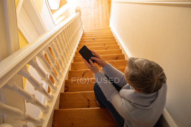 Elevated rear view of a mature Caucasian woman with short grey hair sitting on her stairs at home using a smartphone, with sunlight in the background — Stock Photo