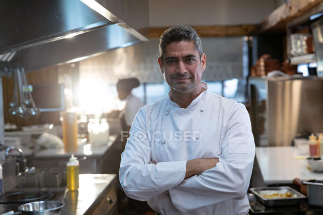 Portrait close up of a smiling middle aged Caucasian male chef wearing whites standing with arms crossed in a restaurant kitchen — Stock Photo