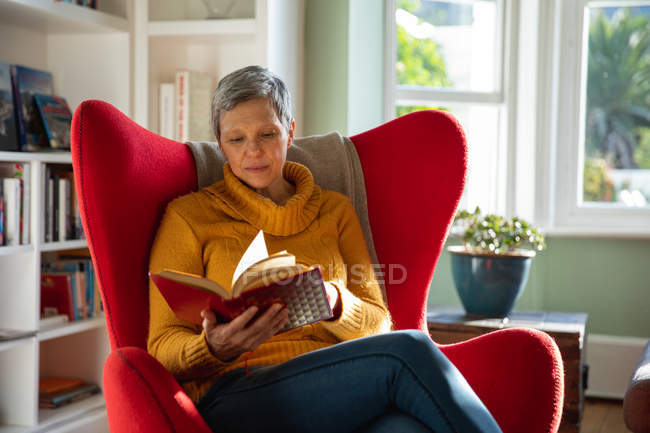 Front view close up of a mature Caucasian woman with short grey hair sitting in a red armchair in her living room reading a book, with a sunlit window in the background — Stock Photo