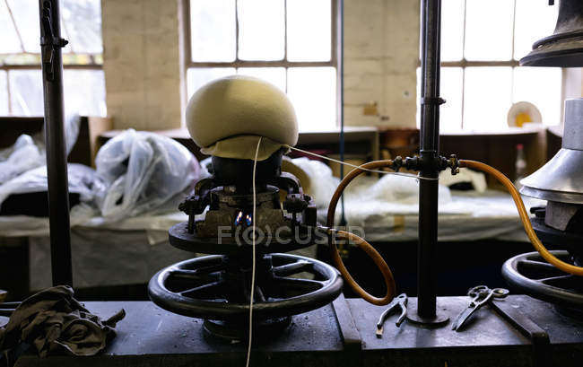 Front view of the top of a hat being shaped on a traditional piece of hat making equipment in the workshop at a hat factory — Stock Photo