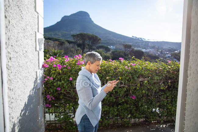 Die Seitenansicht einer reifen kaukasischen Frau mit kurzen grauen Haaren, die mit einem Smartphone in ihrem Garten steht, ist von der Haustür aus zu sehen, mit einer ländlichen Szene und einem Berg im Hintergrund. — Stockfoto