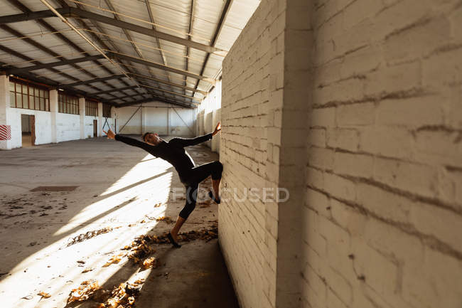 Side view of a young male ballet dancer wearing black dancing against a wall in an empty room at an abandoned warehouse — Stock Photo