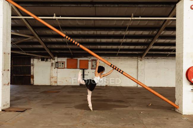 Боковой вид молодой танцовщицы смешанной расы в пуантовых туфлях, стоящей на одной ноге, держа структурный столб в пустой комнате на заброшенном складе — стоковое фото