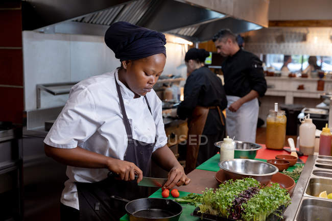 Side view close up of a young African American female chef chopping vegetables in a restaurant kitchen, with other kitchen staff working in the background — Stock Photo