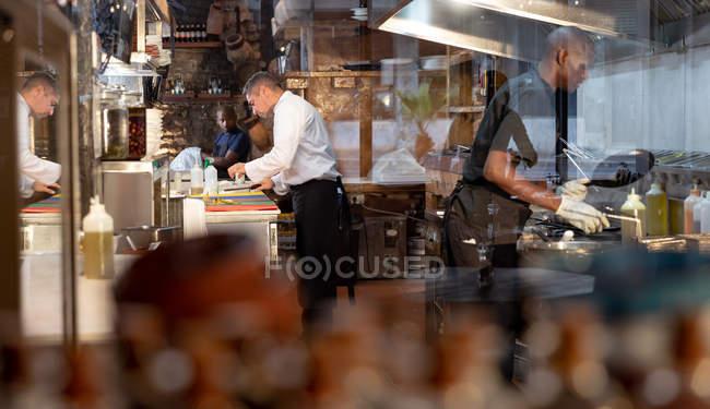 Боковий вид середнього віку Кавказького чоловічого шеф-кухаря і молодого афро-американського чоловічого члена персоналу кухні, що працюють в зайнята ресторан кухні — стокове фото