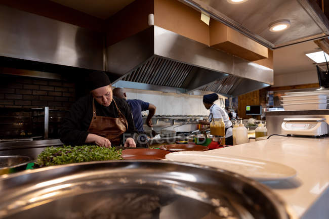 Front view of a young Caucasian female chef chopping ingredients at a counter in a busy restaurant kitchen, seen across a counter and behind kitchen equipment, with other kitchen staff working in the background — Stock Photo