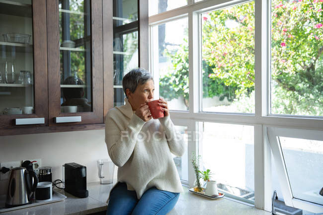 Front view of a mature Caucasian woman with short grey hair sitting on the counter in her kitchen drinking a cup of coffee and looking out of the window, there are trees outside and the sun is shining — Stock Photo