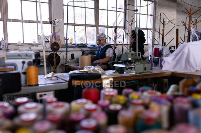 Side view of a middle aged mixed race woman using a sewing machine at a hat factory, surrounded by materials and equipment, with bobbins of colored threads in the foreground — Stock Photo