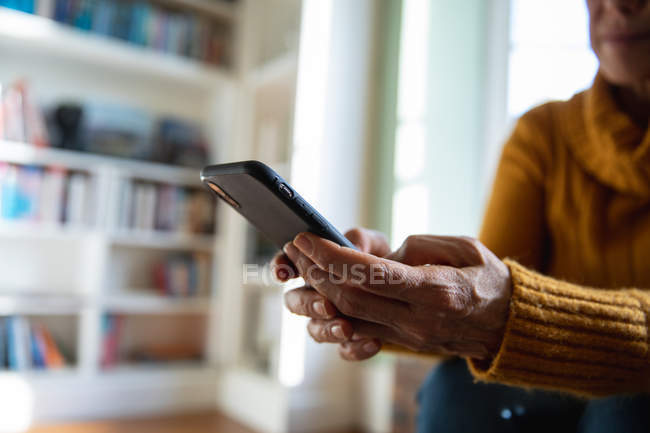 Side view mid section of a mature Caucasian woman sitting at home in her living room using a smartphone, with focus on her hands — Stock Photo