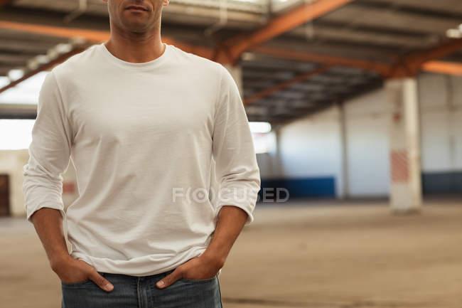 Vista frontale metà sezione di un giovane in piedi con le mani in tasca in una stanza vuota in un magazzino abbandonato — Foto stock