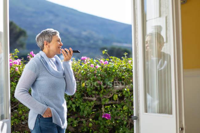 Seitenansicht einer reifen kaukasischen Frau mit kurzen grauen Haaren, die in ihrem Garten steht und mit einem Smartphone spricht, das sie vor dem Mund hält und lächelt. Man sieht sie durch die offenen Türen ihres Hauses, im Hintergrund eine ländliche Szene. — Stockfoto