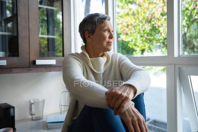 Vista laterale da vicino di una donna caucasica matura con i capelli corti e grigi seduta sul bancone nella sua cucina che guarda fuori dalla finestra, ci sono alberi all'esterno e il sole splende — Foto stock
