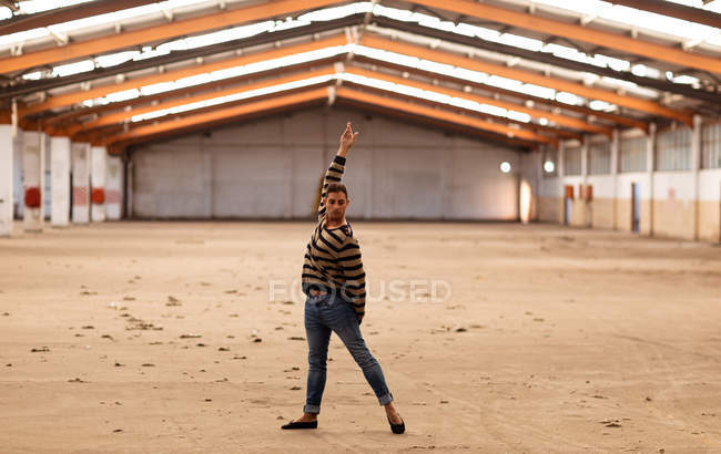 Вид на молодий чоловік балет балерина проведення танцю позу з ARM підняв стоячи в покинутому складі дивлячись на камеру — стокове фото