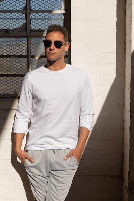 Front view close up of a young man wearing sunglasses standing against a wall in a shaft of sunlight with his hands in his pockets, looking away, at an abandoned warehouse — Stock Photo