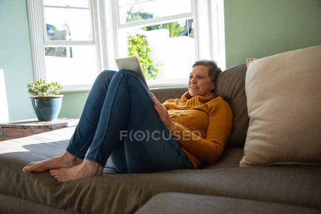 Side view close up of a mature Caucasian woman with short grey hair sitting back with her feet up on a sofa in her living room, smiling and using a tablet computer, a sunlit window in the background — Stock Photo