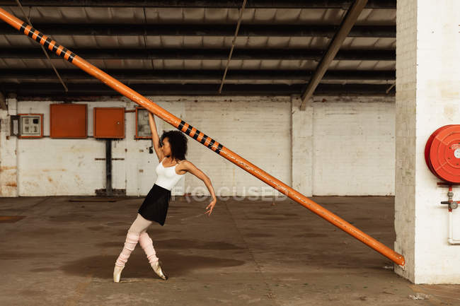 Side view of a young mixed race female ballet dancer wearing pointe shoes dancing on her toes holding a structural pole in an empty room at an abandoned warehouse — Stock Photo