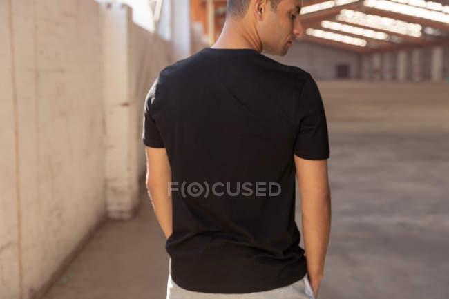 Visão traseira de perto de um jovem vestindo uma camiseta preta, de pé com a cabeça virada para o lado em um armazém abandonado — Fotografia de Stock