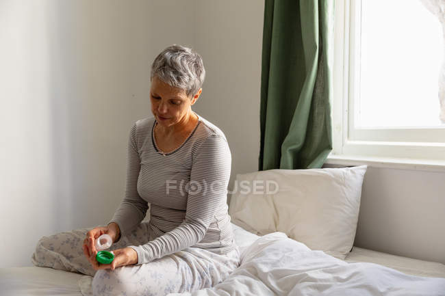 Front view close up of a mature Caucasian woman with short grey hair sitting on her bed taking medication at home — Stock Photo