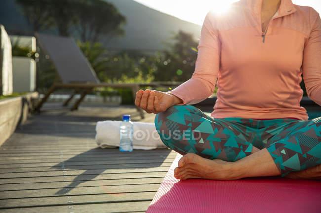 Vista frontal sección baja de mujer con ropa deportiva sentada en una alfombra en una posición de yoga meditando en su jardín, retroiluminada por la luz del sol con una vista rural en el fondo - foto de stock