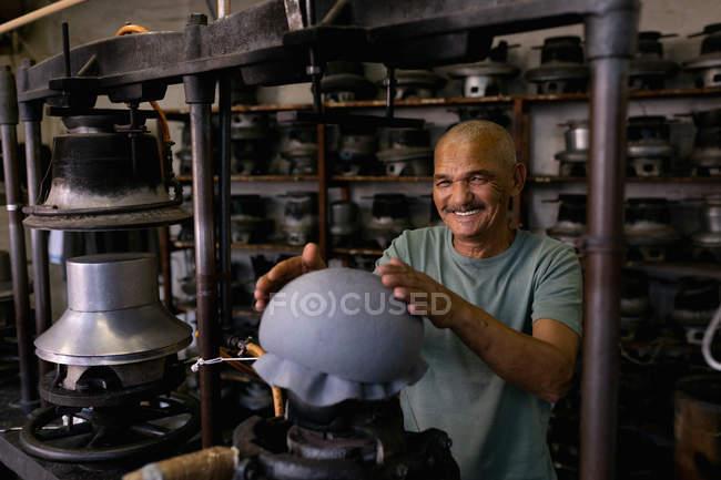 Портрет улыбающегося старшеклассника со смешанной расой, держащего руки над верхушкой шляпы, которая была сформирована на части оборудования в мастерской на шляпной фабрике — стоковое фото