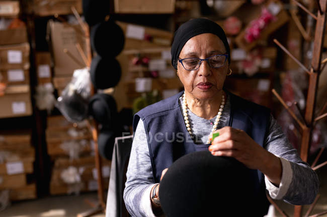 Front view close up of a middle aged mixed race woman holding and adding the finishing touches to a small hat in the workshop at a hat factory, with boxes of materials in the background — Stock Photo