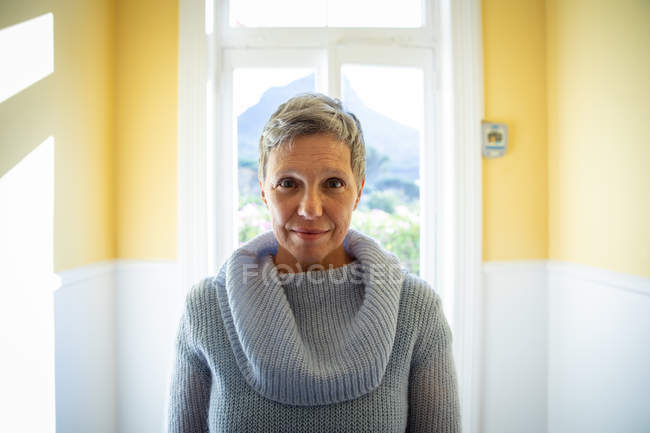 Портрет зрелой кавказской женщины с короткими седыми волосами в свитере с капюшоном, стоящей перед окном дома, смотрящего прямо в камеру и улыбающейся, с видом на сельскую местность на заднем плане — стоковое фото