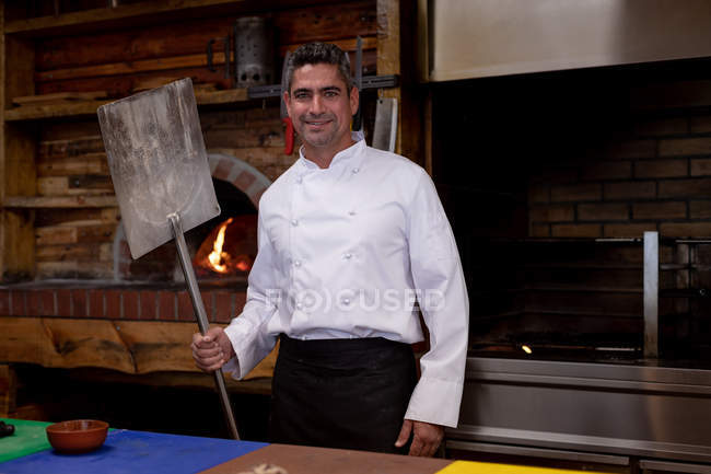 Portrait close up of a smiling middle aged Caucasian male chef holding a pizza peel and standing by a pizza oven in a restaurant kitchen — Stock Photo
