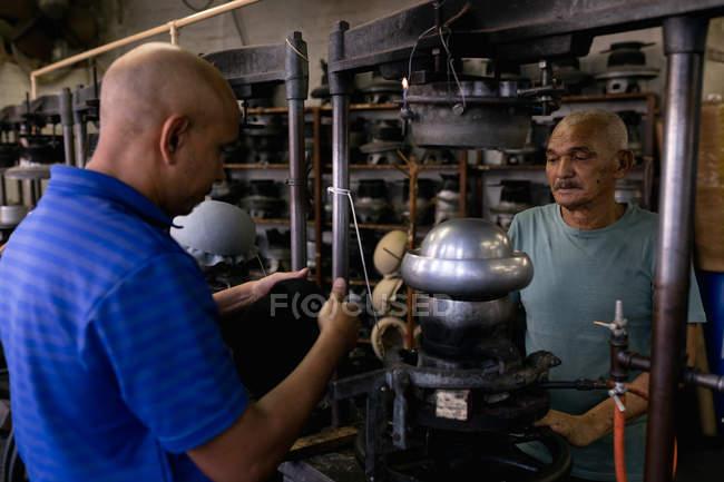 Vista lateral de perto de um idoso e um mestiço de meia-idade trabalhando juntos em uma máquina na oficina em uma fábrica de chapéus, o homem mais jovem segurando um chapéu em suas mãos, com equipamentos visíveis no fundo — Fotografia de Stock