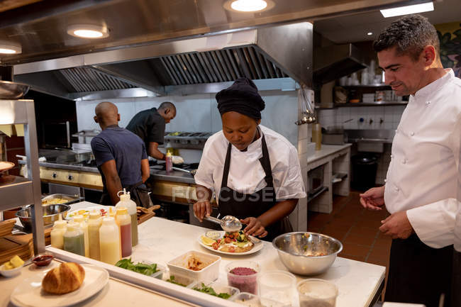 Side view close up of a middle aged Caucasian male chef overseeing a young African American female chef plating up a dish in a restaurant kitchen, with kitchen staff busy working in the background — Stock Photo
