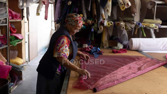 Side view of a middle aged mixed race woman standing at a table working with fabric at a hat factory. — Stock Photo