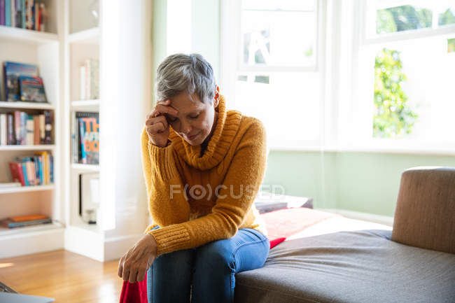 Front view close up of a mature Caucasian woman with short grey hair sitting at home in her living room looking down with her head leaning on her hand, a sunlit window in the background — Stock Photo