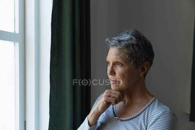 Side view close up of a mature Caucasian woman with short grey hair standing and looking out of the window at home with her hand under her chin — Stock Photo