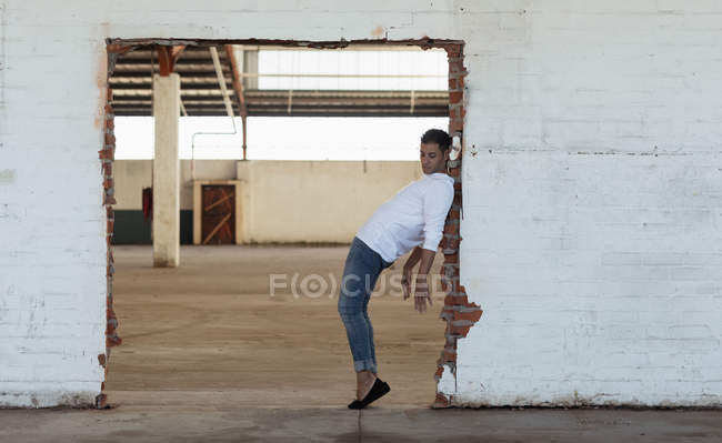 Side view of a young male ballet dancer wearing jeans posing in a doorway in an empty room at an abandoned warehouse — Stock Photo