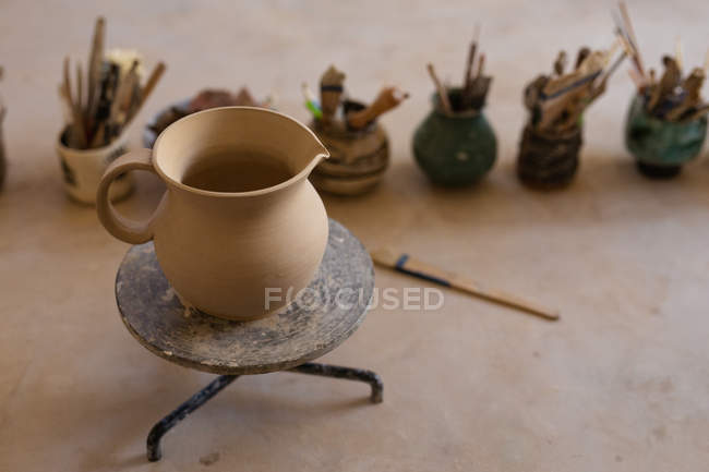 Elevated view of a clay jug on a banding wheel sitting on a work top at a pottery studio, with pots and tools in the background — Stock Photo