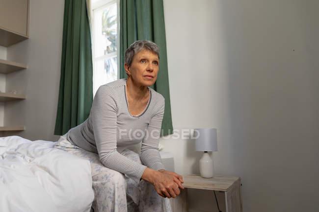 Visão lateral close-up de uma mulher branca madura com cabelos brancos curtos sentados ao lado de sua cama em casa com as mãos apertadas, olhando para longe — Fotografia de Stock