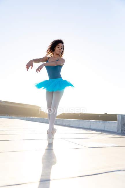 Vista frontal de cerca de una joven bailarina de ballet de raza mixta con un tutú azul y zapatos puntiagudos bailando en la azotea de un edificio urbano, retroiluminado por la luz del sol - foto de stock