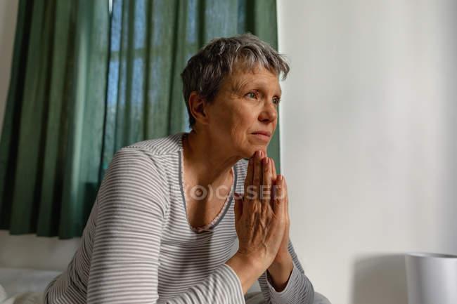 Вид збоку крупним планом зрілої кавказької жінки з коротким сивим волоссям сидить на ліжку вдома руки разом, як якби в молитві, дивлячись — стокове фото