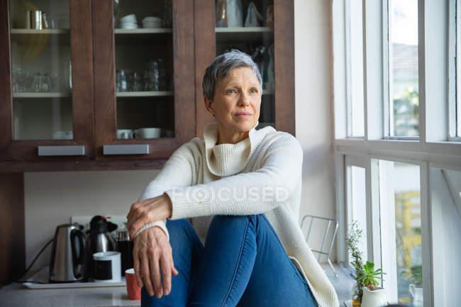 Nahaufnahme einer reifen kaukasischen Frau mit kurzen grauen Haaren, die in ihrer Küche auf dem Tresen sitzt und aus dem Fenster schaut — Stockfoto