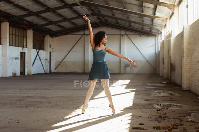 Front view of a young mixed race female ballet dancer standing on her toes with arms raised in a shaft of sunlight while dancing in an empty room at an abandoned warehouse — Stock Photo