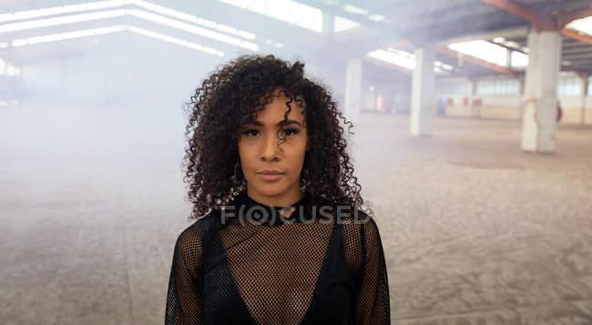 Retrato de uma jovem mulher de raça mista com cabelo encaracolado de comprimento de ombro usando um top de malha preta olhando diretamente para a câmera em um armazém abandonado — Fotografia de Stock